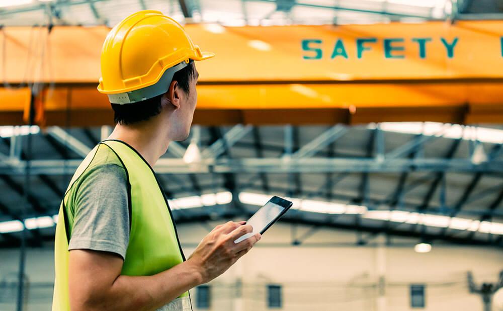 Un homme en tenue de travail de sécurité regarde un local avec son téléphone à la main.