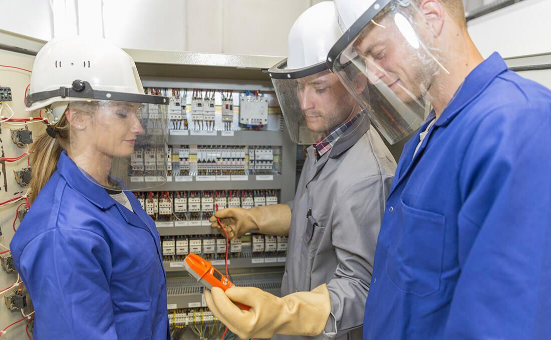 Trois personnes font des tests devant une installation électrique.