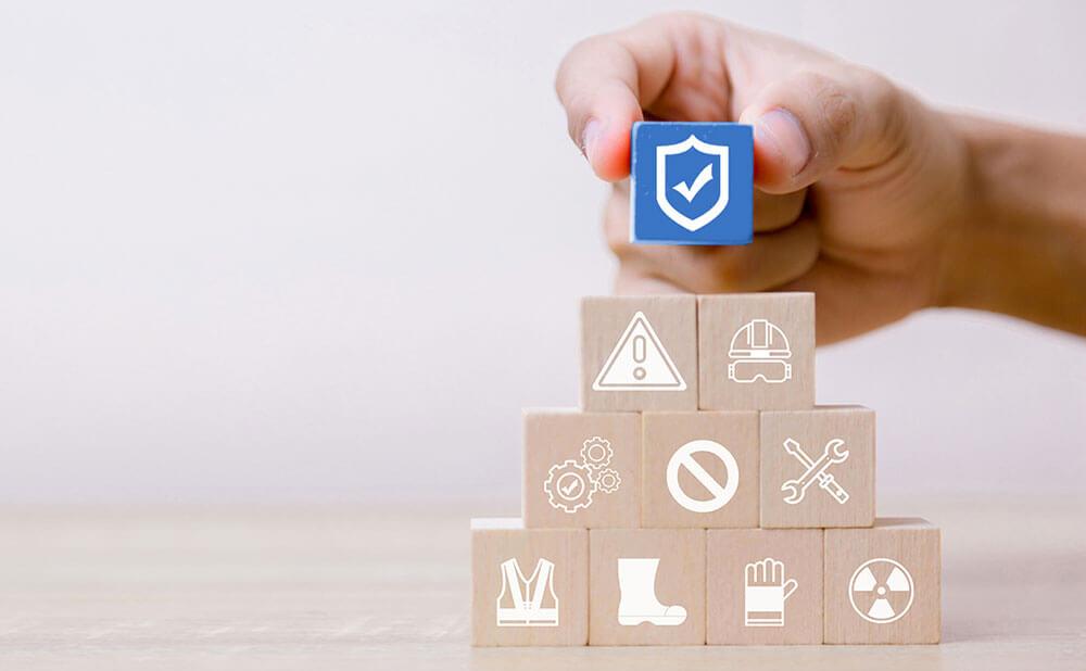Plusieurs cubes les uns sur les autres forment une petite pyramide. Chaque cube a une illustration d\'un thème sur la sécurité. Celui tout en haut est le seul coloré et c\'est le logo de la sécurité.