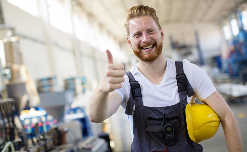 Un homme est dans un entrepôt. Il sourit avec un ponce en l\'air et tient son casque jaune de l\'autre main.