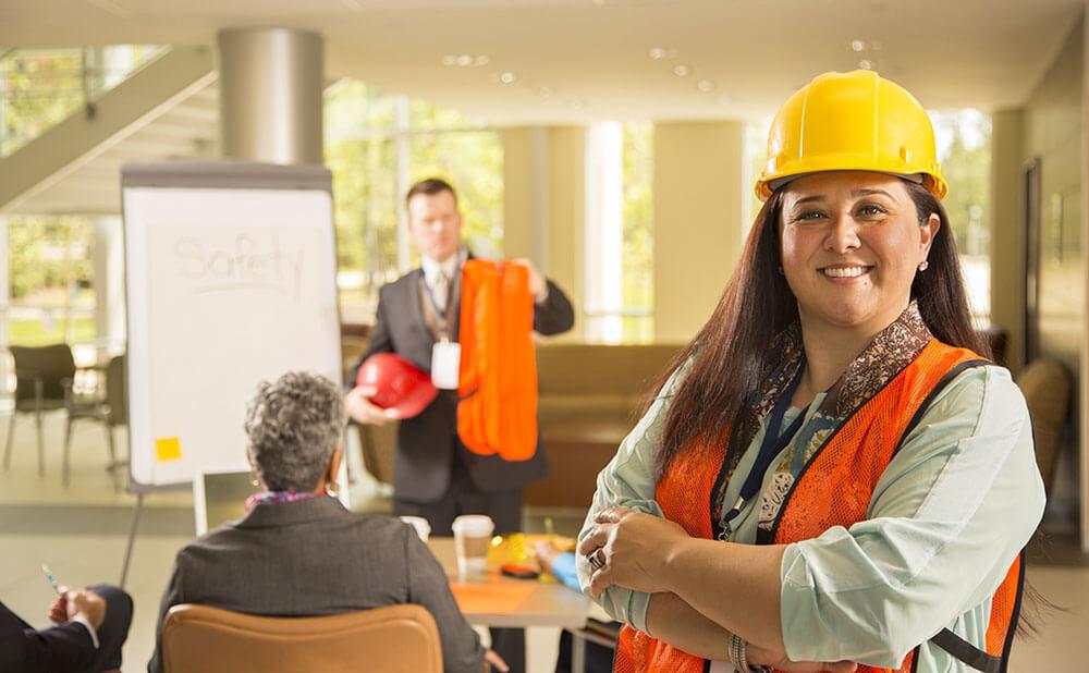 Une femme en tenue de travail de sécurité sourit. Derrière elle il y a une réunion et un homme présente du matériel de sécurité.