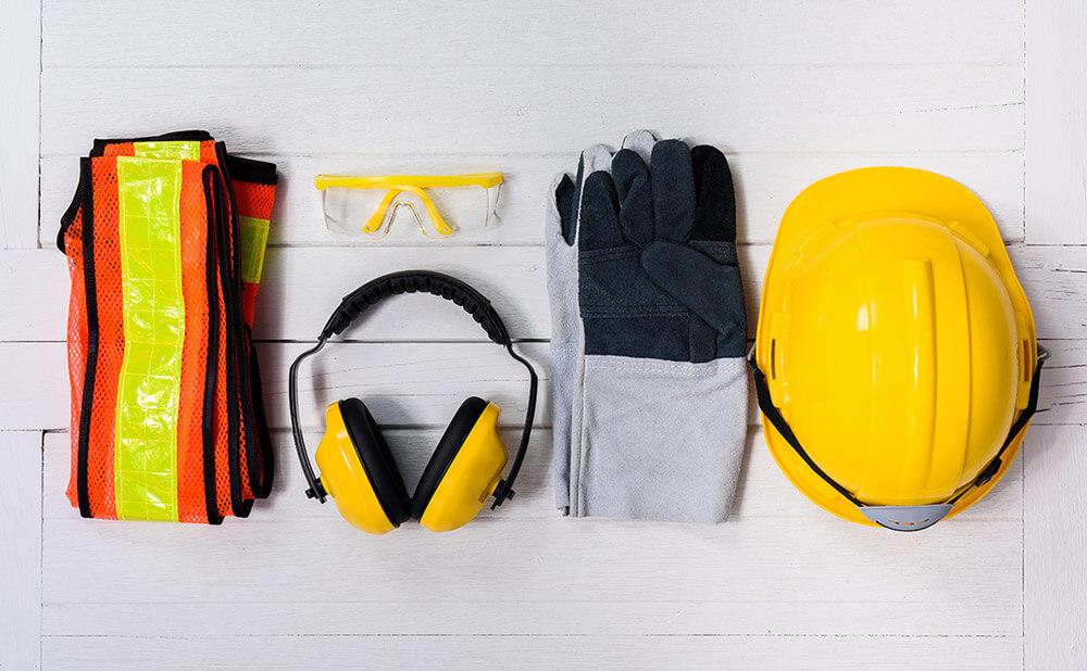 Photo avec des équipements de protection : gilet jaune, casque, gants, lunettes et casque pour les oreilles.