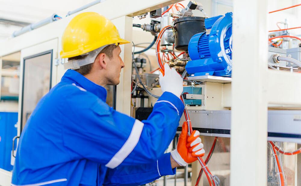 Homme en tenue de travaille de protection qui fait de la maintenance industrielle