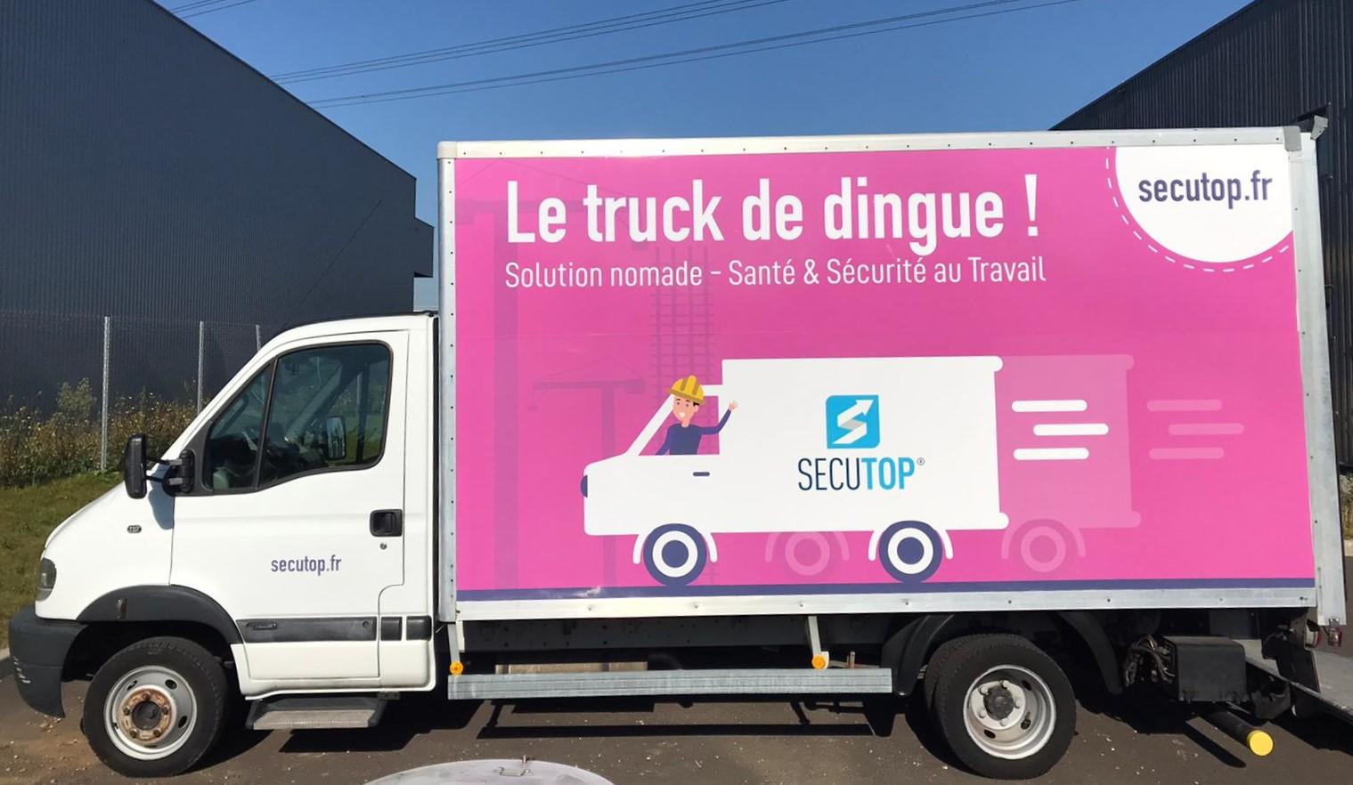 """Photo du secutruck : notre camion santé et sécurité au travail avec comme slogan \""""Le truck de dingue !\"""""""
