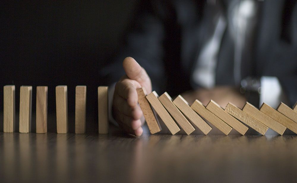 Des dominos sont en train de tomber mais une main et au milieu et arrête la chute des dominos.