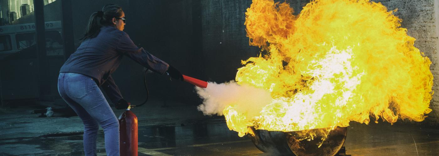 femme avec un extincteur combattant le feu