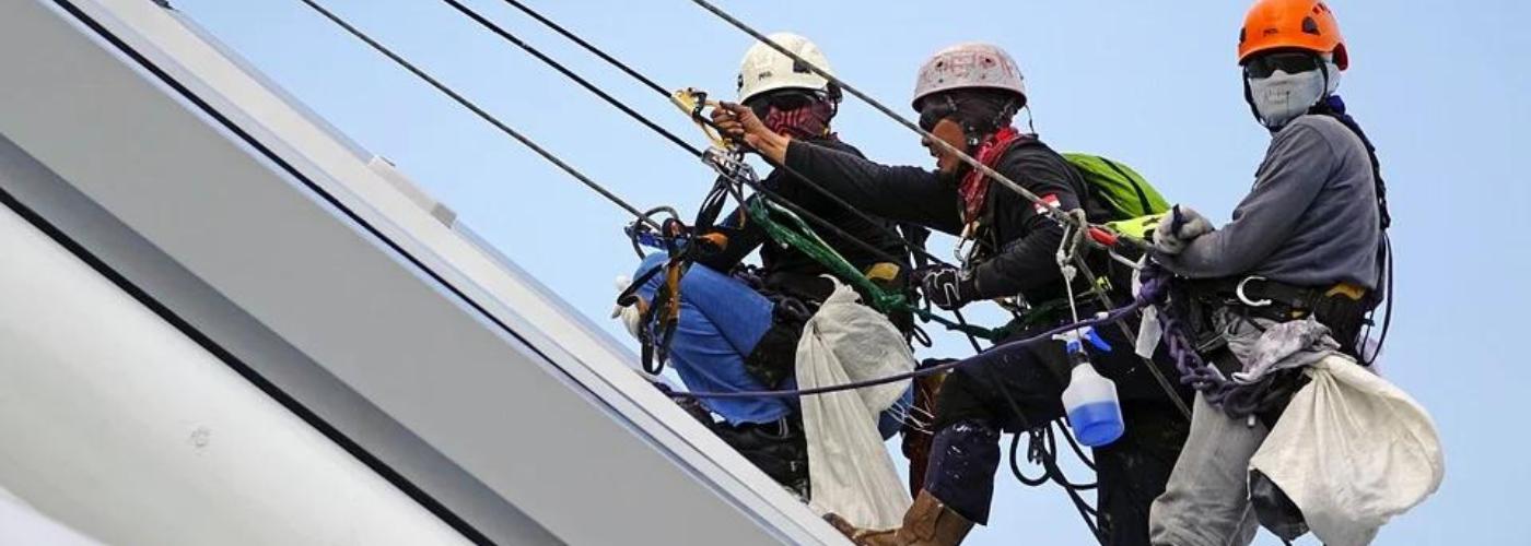 3 hommes travaillant en hauteur avec casques et harnais