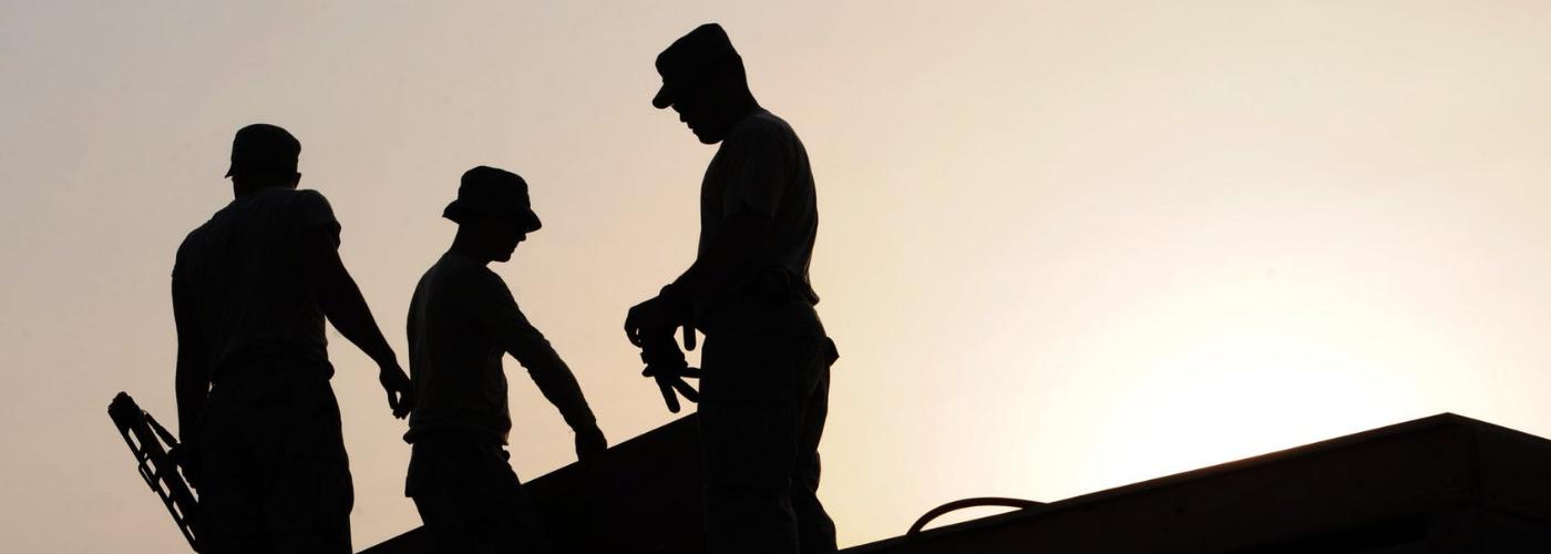 trois hommes travaillant sur un toit en fin de journée