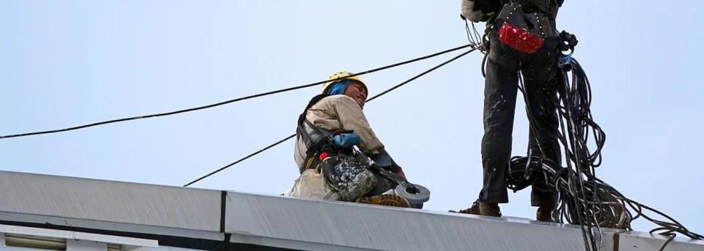 deux hommes travaillant en hauteur avec casques et harnais