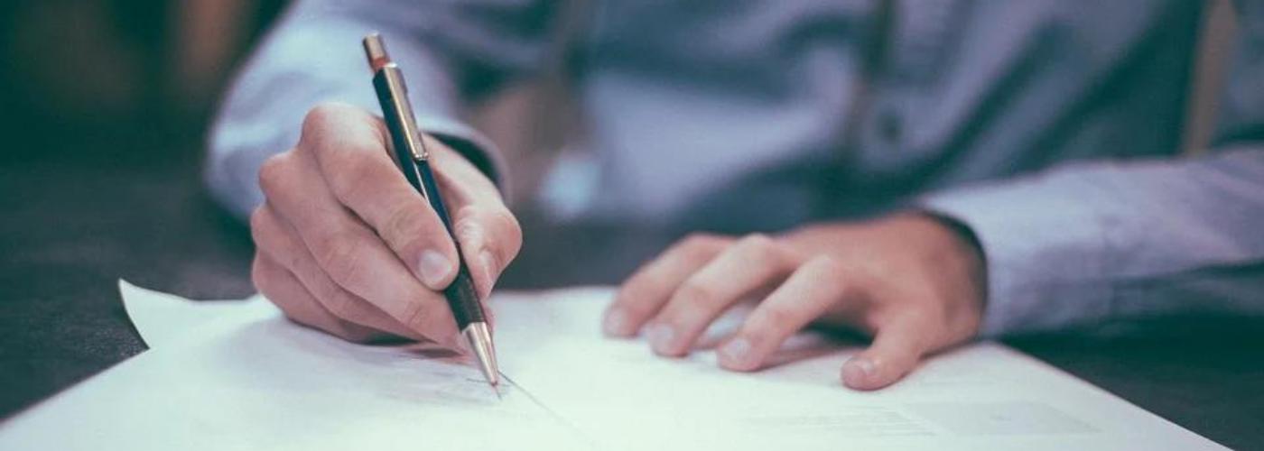 homme tenant un stylo entrain de signer des documents