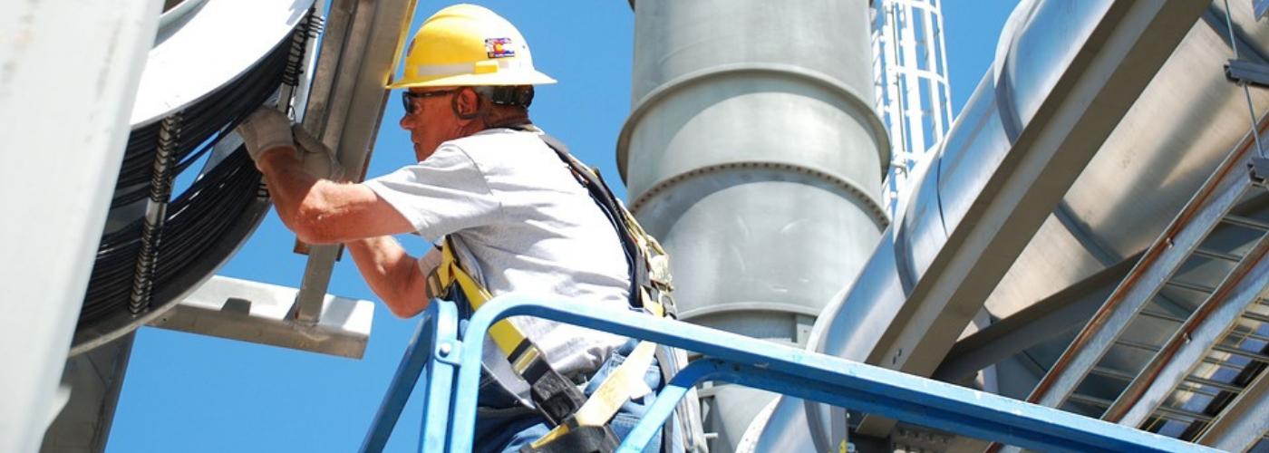 homme travaillant en hauteur avec un casque jaune