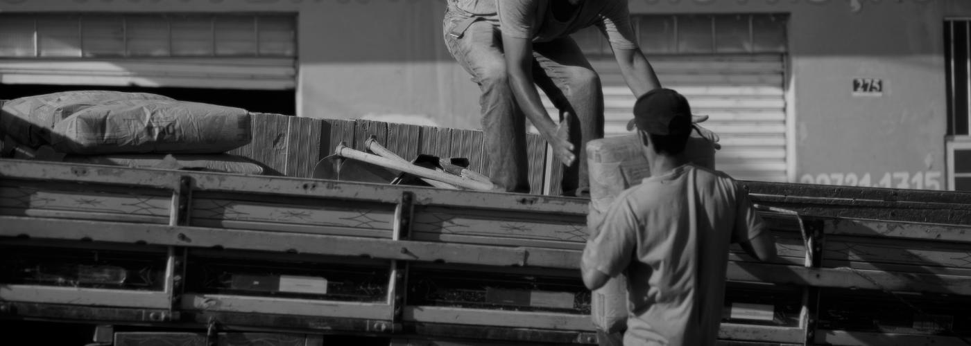deux hommes posant une charge lourde à l\'arrière d\'un camion